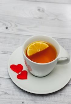 Kopje thee met hartjes op houten tafel, minimaal concept van valentijnsdag ochtendontbijt