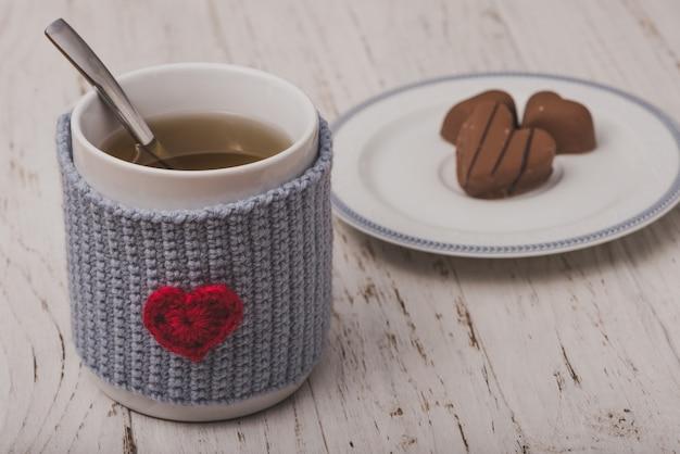 Kopje thee met hartvormige chocolaatjes