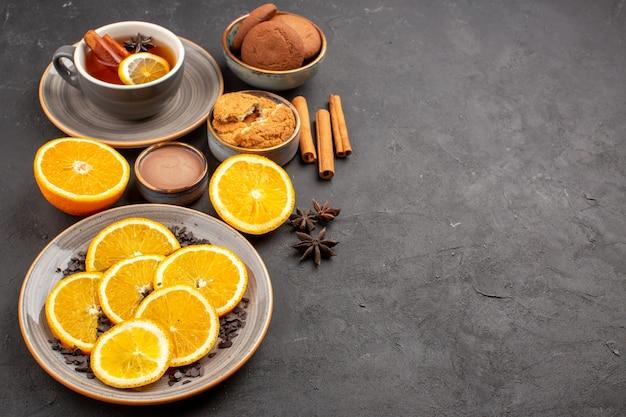 Kopje thee met koekjes en vers gesneden sinaasappelen op donker