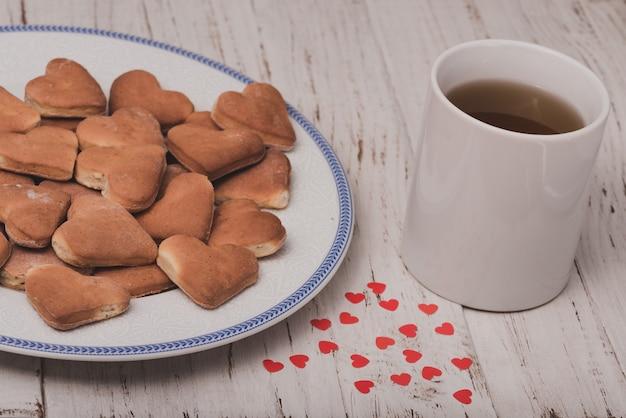 Kopje thee met koekjes naast