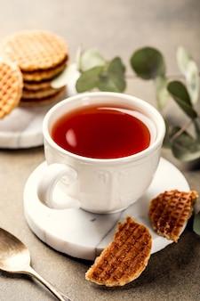 Kopje thee met mini stroopwafel, stroopwafels koekjes en eucalyptustakjes op lichte ondergrond