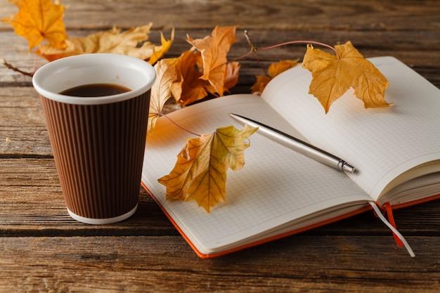 Kopje thee met oud boek, herfstbladeren op houten tafel