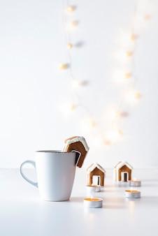 Kopje thee met peperkoekhuis en kaarsen op witte achtergrond. kerstlichten. verticaal frame.