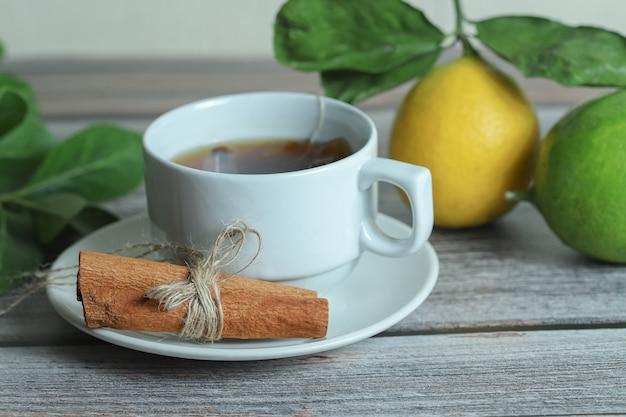 Kopje thee met pijpjes kaneel en citroen op houten oppervlakte.