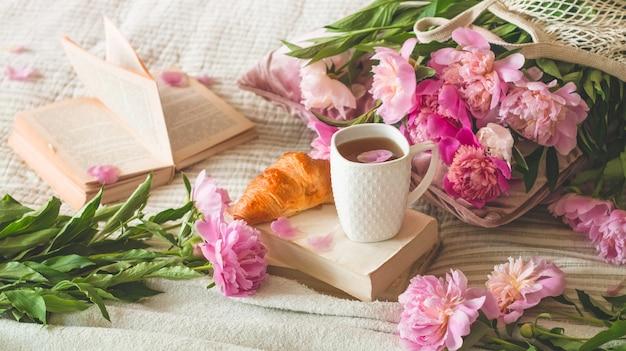 Kopje thee met pions-bloemen en lentedecor op de boeken
