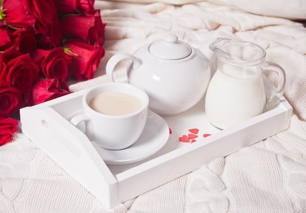 Kopje thee met rode rozen op een wit dienblad