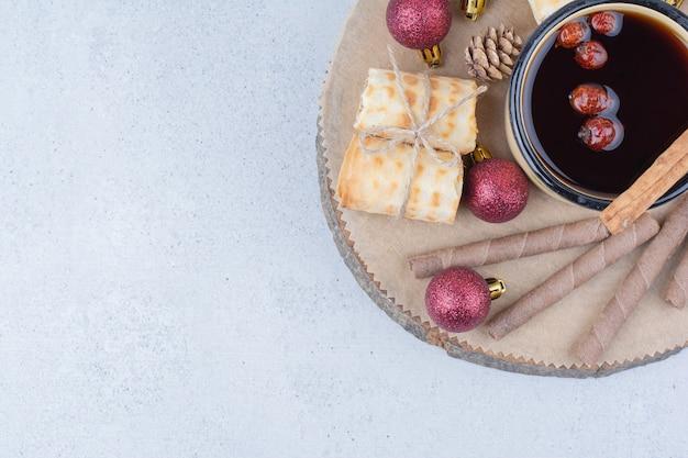 Kopje thee met rozenbottels, koekjes en kerstballen op een houten bord.