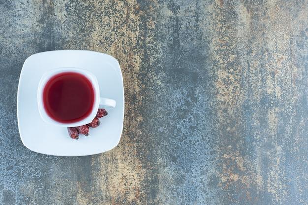 Kopje thee met rozenbottels op marmer.