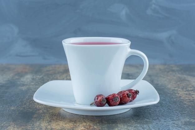 Kopje thee met rozenbottels op marmeren tafel.
