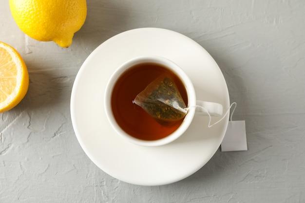 Kopje thee met theezakje en citroenen op grijs, bovenaanzicht