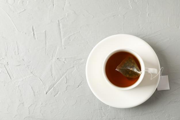 Kopje thee met theezakje op grijze, bovenaanzicht