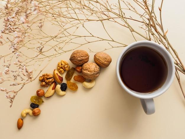 Kopje thee, noten en rozijnen naast gedroogde bloemen