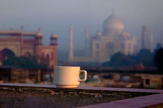 Kopje thee op de achtergrond van de taj mahal beroemdste bezienswaardigheid. ontbijt op het dak van het gebouw in agra. indië.