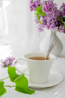 Kopje thee op een lichte tafel in de buurt van een raam in de ochtend en trossen