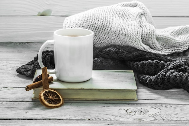 Kopje thee op een mooie houten muur met winterse trui, oud boek