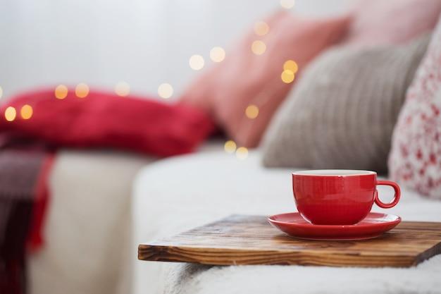 Kopje thee op houten dienblad op bank
