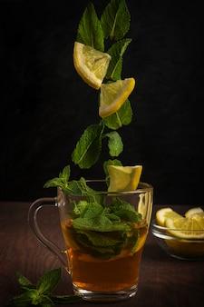 Kopje thee op houten tafel met vliegende schijfjes citroen en muntblaadjes tegen donker