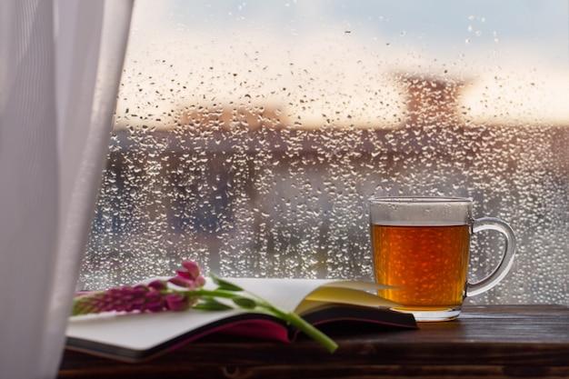 Kopje thee op van raam met regendruppels bij zonsondergang
