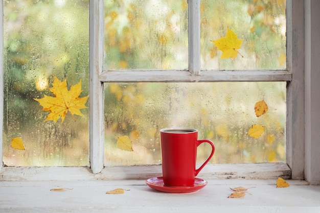 Kopje thee op witte houten vensterbank in de herfst