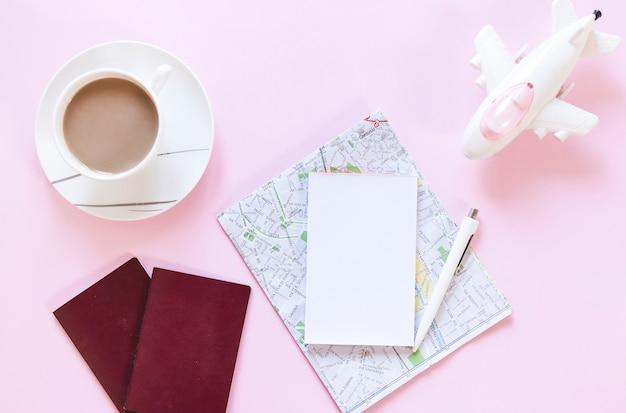 Kopje thee; paspoort; kaart; papier; pen en vliegtuig op roze achtergrond