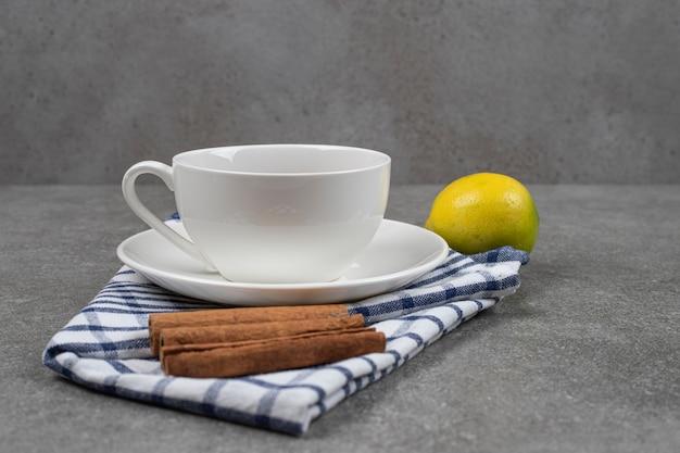 Kopje thee, pijpjes kaneel en citroen op marmeren oppervlakte