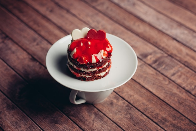 Kopje thee rode cake op een schotel snoepjes dessert houten achtergrond