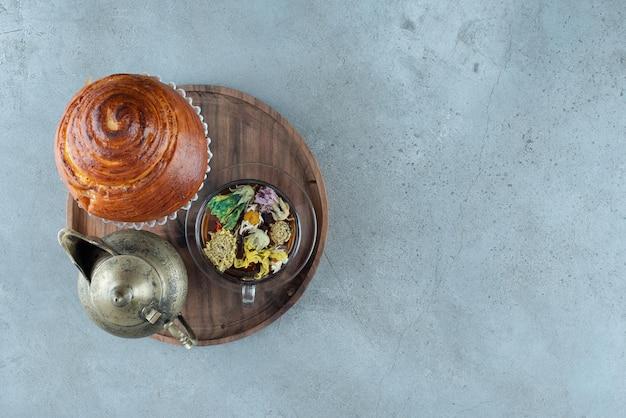 Kopje thee, theekopje en gebak op houten plaat.