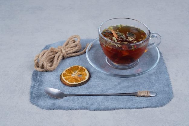 Kopje thee, touw en gedroogde sinaasappelschijf op tafellaken.