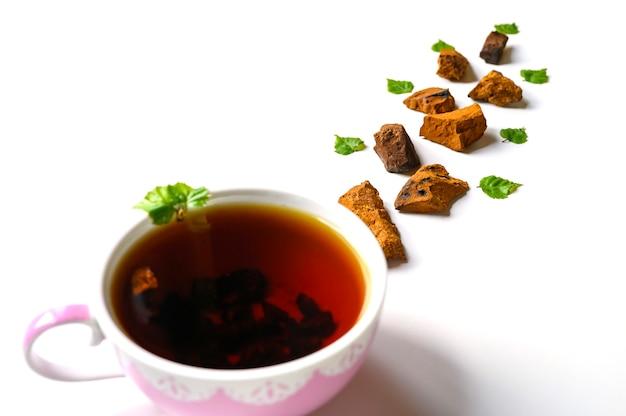 Kopje thee van berkchaga-paddenstoel en gemalen chaga-schimmelstukken voor geïsoleerd theebrouwen