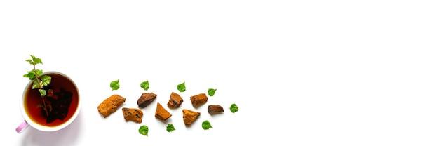 Kopje thee van berkchaga-paddenstoel en gemalen stukjes chaga-schimmel voor het zetten van thee