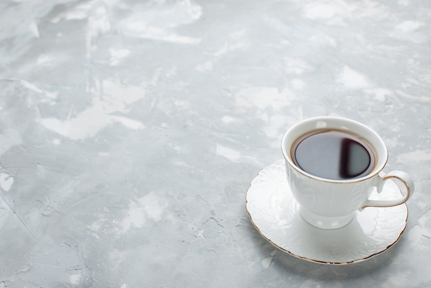 Kopje thee warm van binnen witte kop op glazen plaat op licht bureau, zoete thee drinken