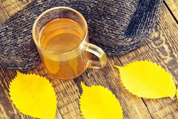 Kopje thee, zwarte gebreide sjaal en gele herfstbladeren op houten ondergrond