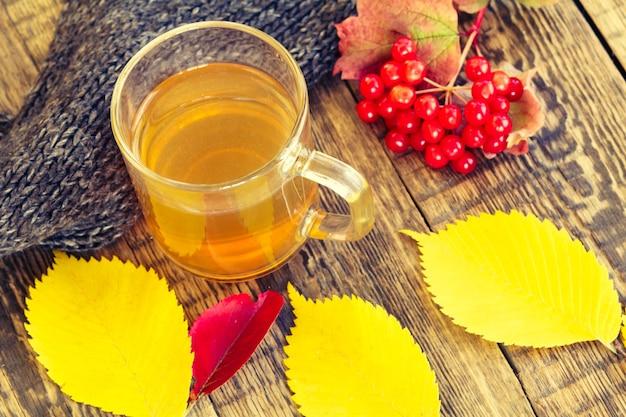 Kopje thee, zwarte gebreide sjaal, viburnumtak en gele herfstbladeren op houten ondergrond