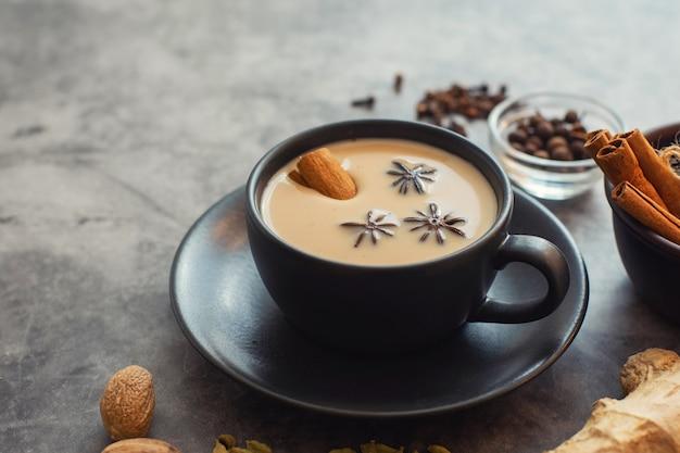 Kopje traditionele indiase masala chai thee met ingrediënten
