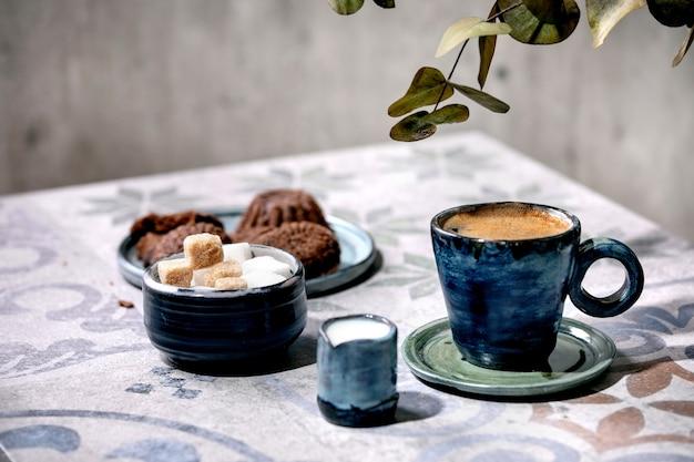 Kopje turkse zwarte koffie met melk, suikerklontjes en koekjes op sierlijke keramische tafel met takken van eucalyptus. zonlicht, schaduwen