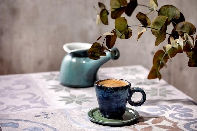 Kopje turkse zwarte schuimige koffie op sierlijke keramische tafel met koffiepot cezve en eucalyptustakken