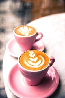 Kopje van twee warme kopjes latte koffie op marmeren tafel achtergrond