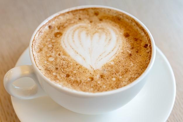 Kopje vers gezette cappuccino met latte art schuim op een tafel van de cafetaria.