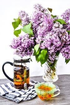 Kopje verse kruidenthee, theepot en bloesem violet lila bloemen boeket in glazen vaas, keuken interieur decoraties.