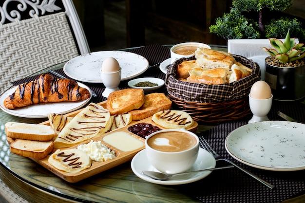 Kopje warme cappuccino en chocolade croissant met ontbijt