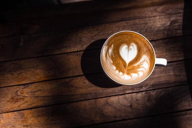 Kopje warme cappuccino is op houten tafel achtergrond. de zon schijnt op de tafel.