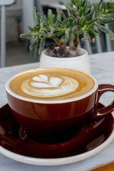 Kopje warme cappuccino met schuimige schuimkunst op tafel