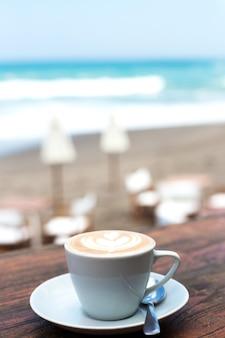 Kopje warme cappuccino op houten tafel achtergrond met uitzicht op de oceaan achtergrond. vakantieconcept.