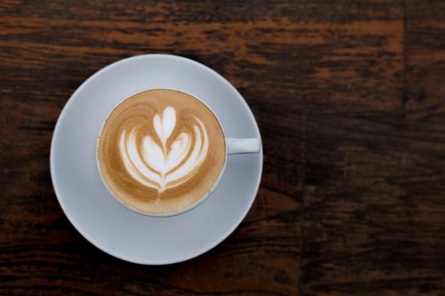 Kopje warme cappuccino op houten tafel achtergrond. platliggende stijl