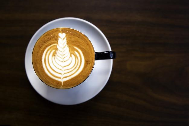Kopje warme cappuccino staat op de houten tafel. het is een kunst op de latte.