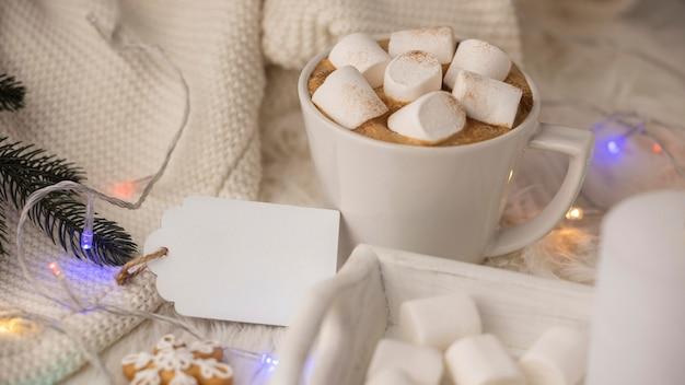 Kopje warme chocolademelk met marshmallows en trui met tag