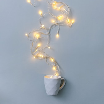 Kopje warme drank en slinger met gloeilampen op grijze achtergrond minimale winter vieringen concept
