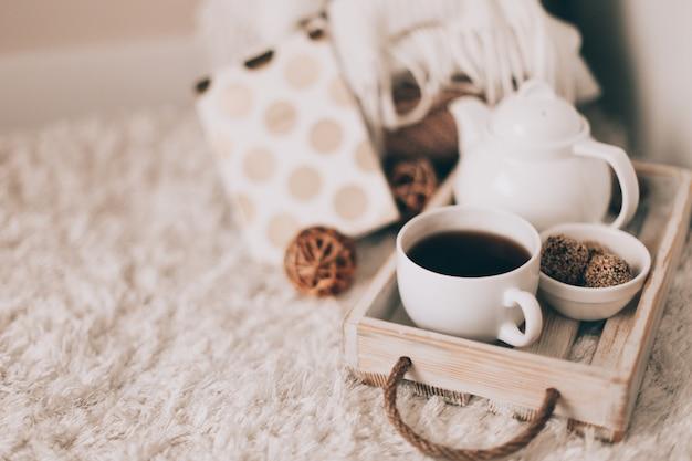 Kopje warme drank en theepot op een dienblad, kleding breien