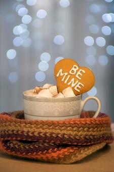 Kopje warme en aromatische koffie met marshmallow en hartkoekje met be mine-zin op blauwe kerstverlichting