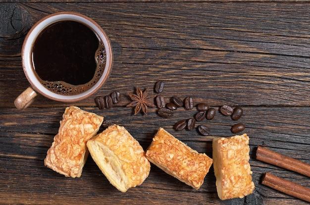 Kopje warme koffie en bladerdeeg koekjes met kaas op donkere houten tafelblad weergave